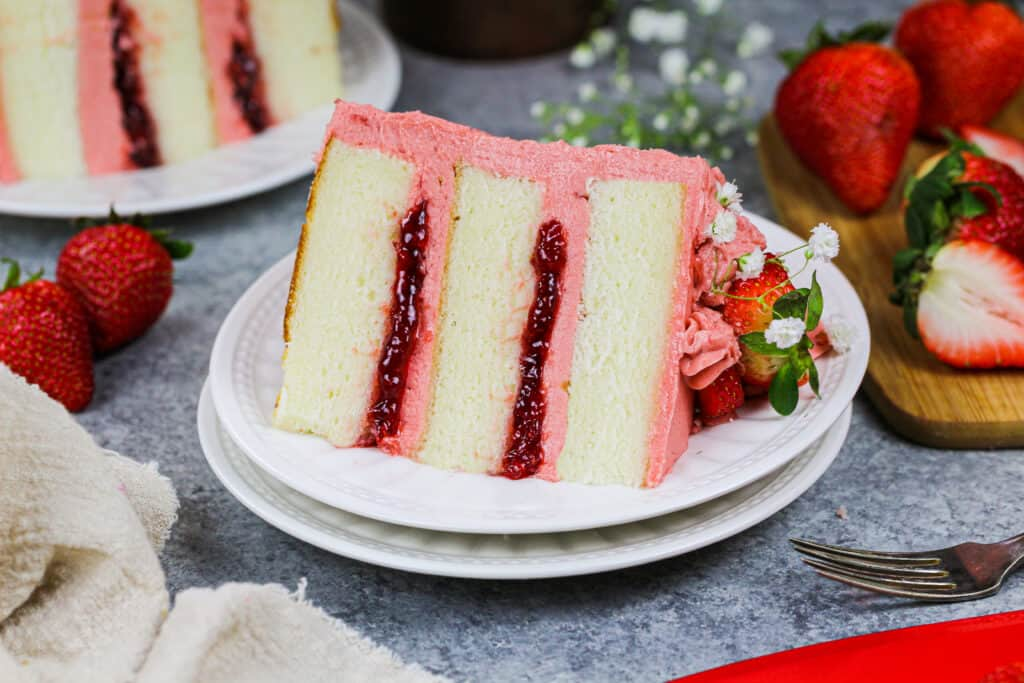 image of a slice of vanilla strawberry cake filled with strawberry jam and strawberry frosting