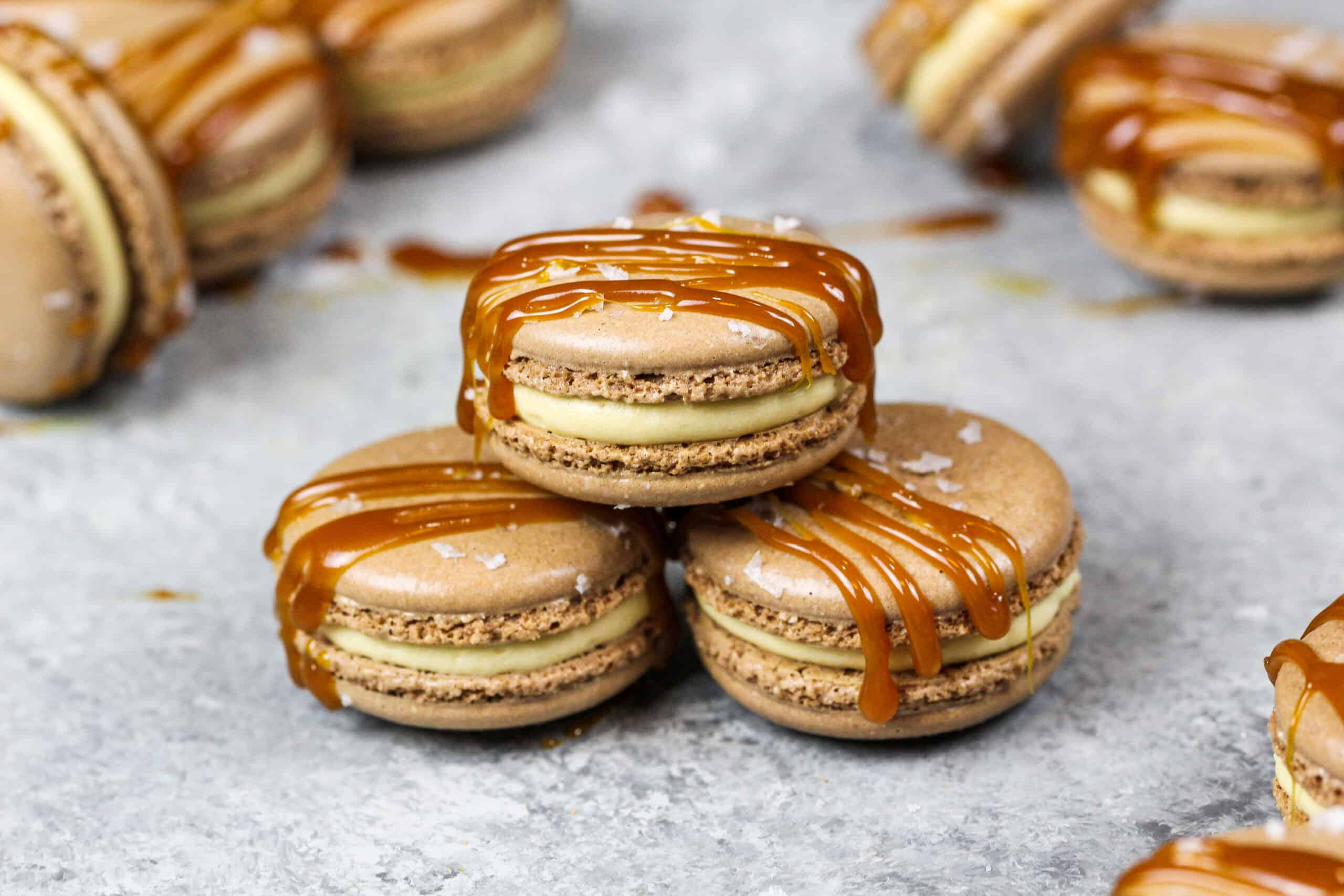 image of salted caramel macarons drizzled with caramel sauce and flakey sea salt