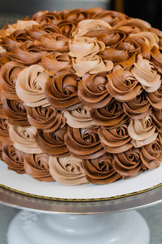 image of chocolate buttercream cake decorated with buttercream rosettes