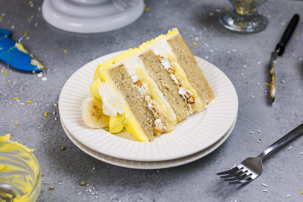 image of a slice of banana pudding cake made with layers of banana cake, pudding, bananas, whipped cream and vanilla wafers