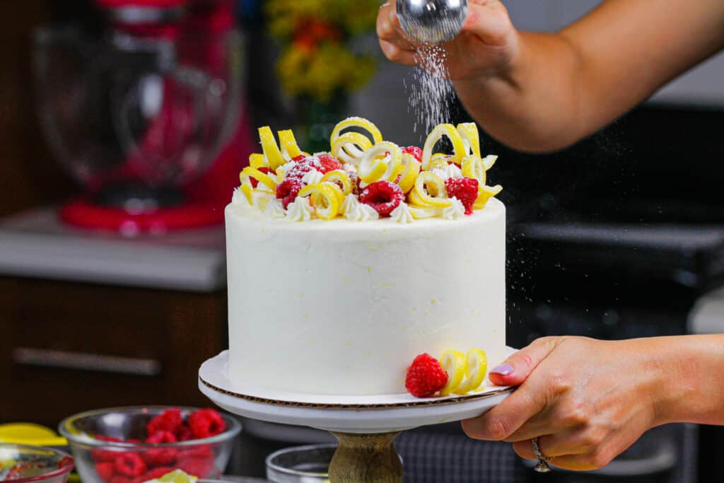 image of lemon raspberry layer cake being dusted with powdered sugar