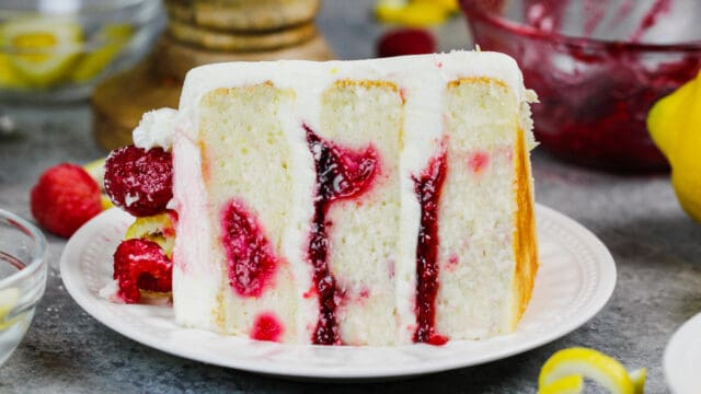 image of a slice of lemon rapsberry cake on a plate, showing it's raspberry filling and lemon cream cheese frosting
