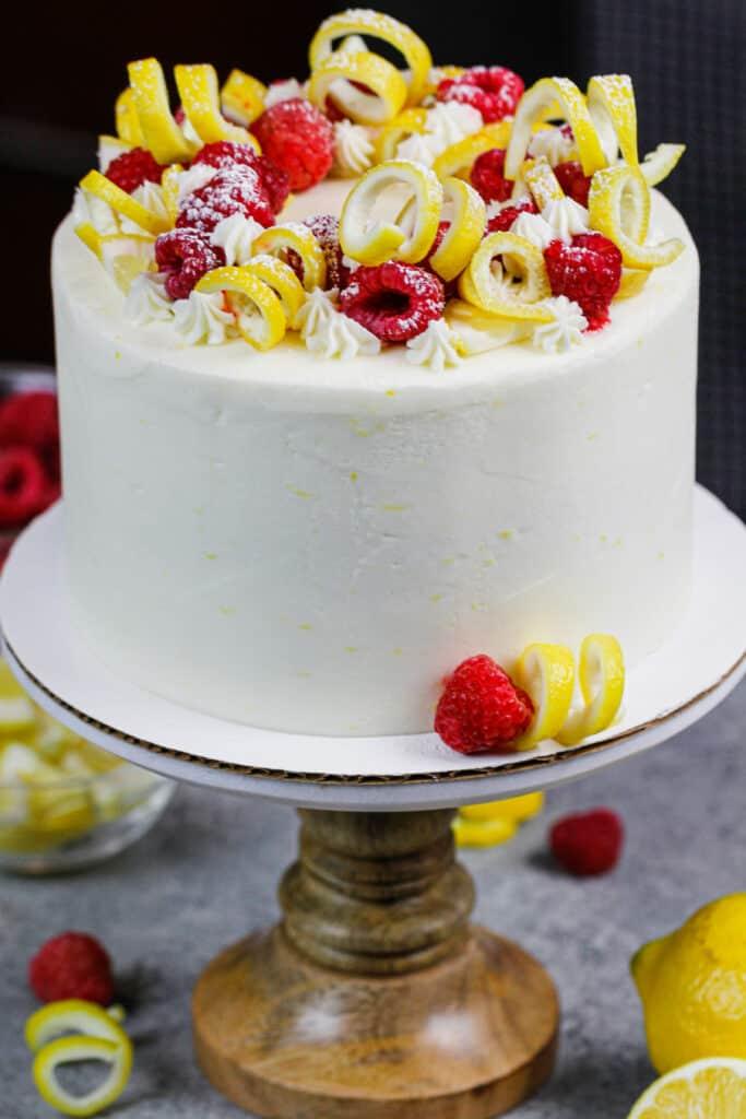image of lemon raspberry cake decorated with lemon spirals and fresh raspberries