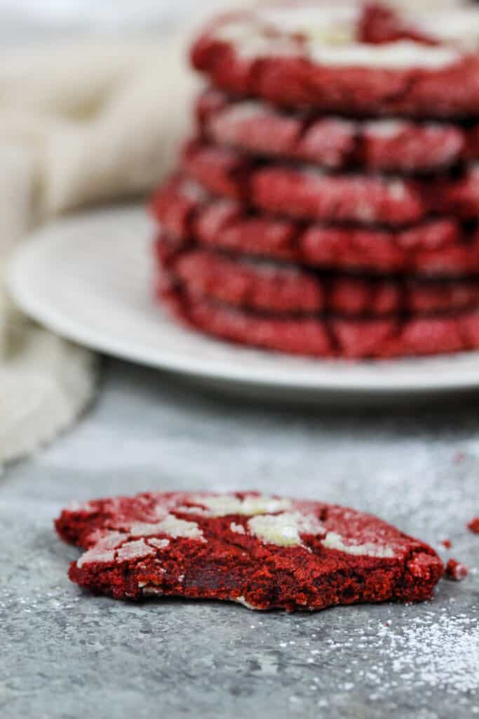 image of a red velvet crinkle cookie that's been bitten into to show it's soft and chewy center