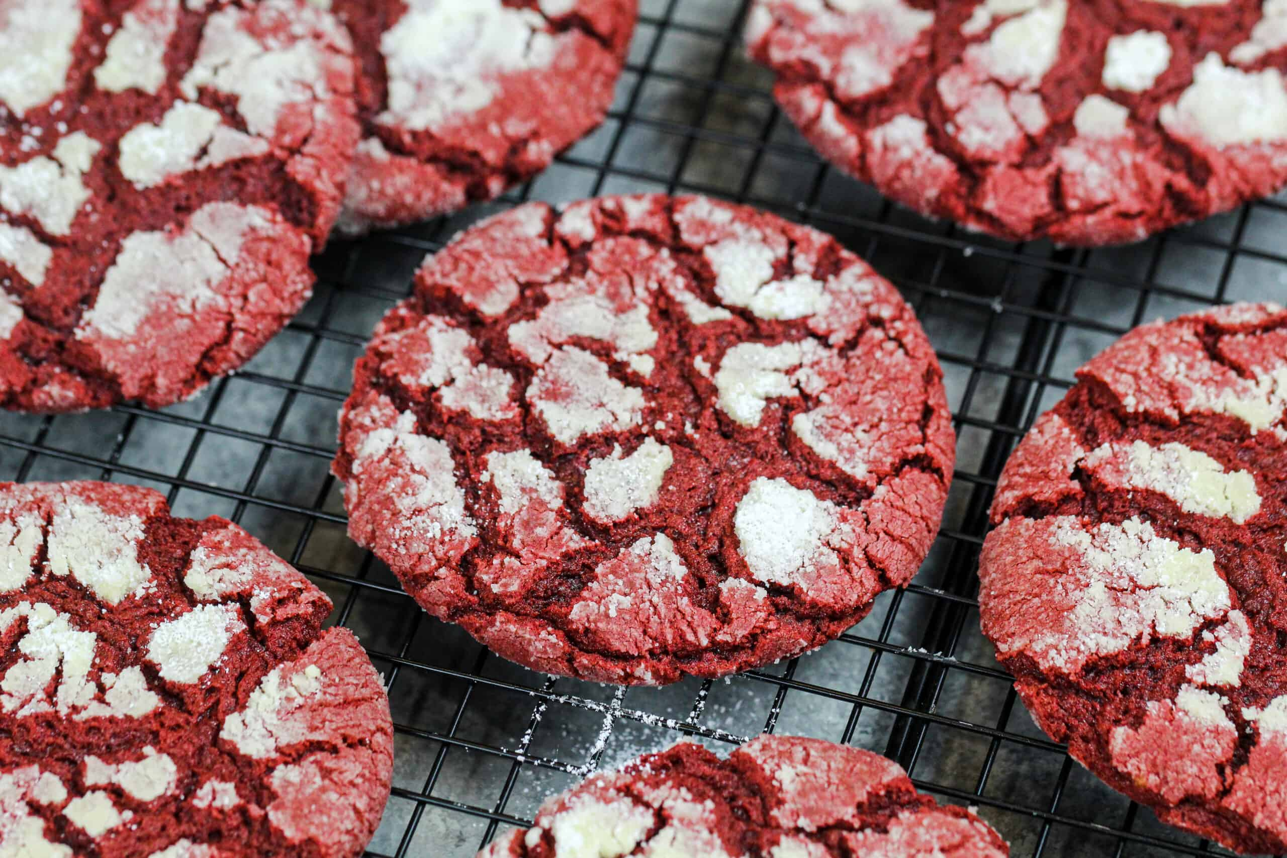 image of red velvet crinkle cookies made from scratch cooling on a wire rack