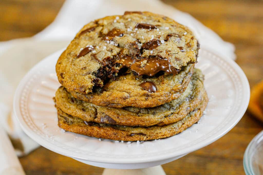 image of brown butter Nutella chocolate chip cookies in a stack with the top cookie bitten into showing the warm, melting nutella