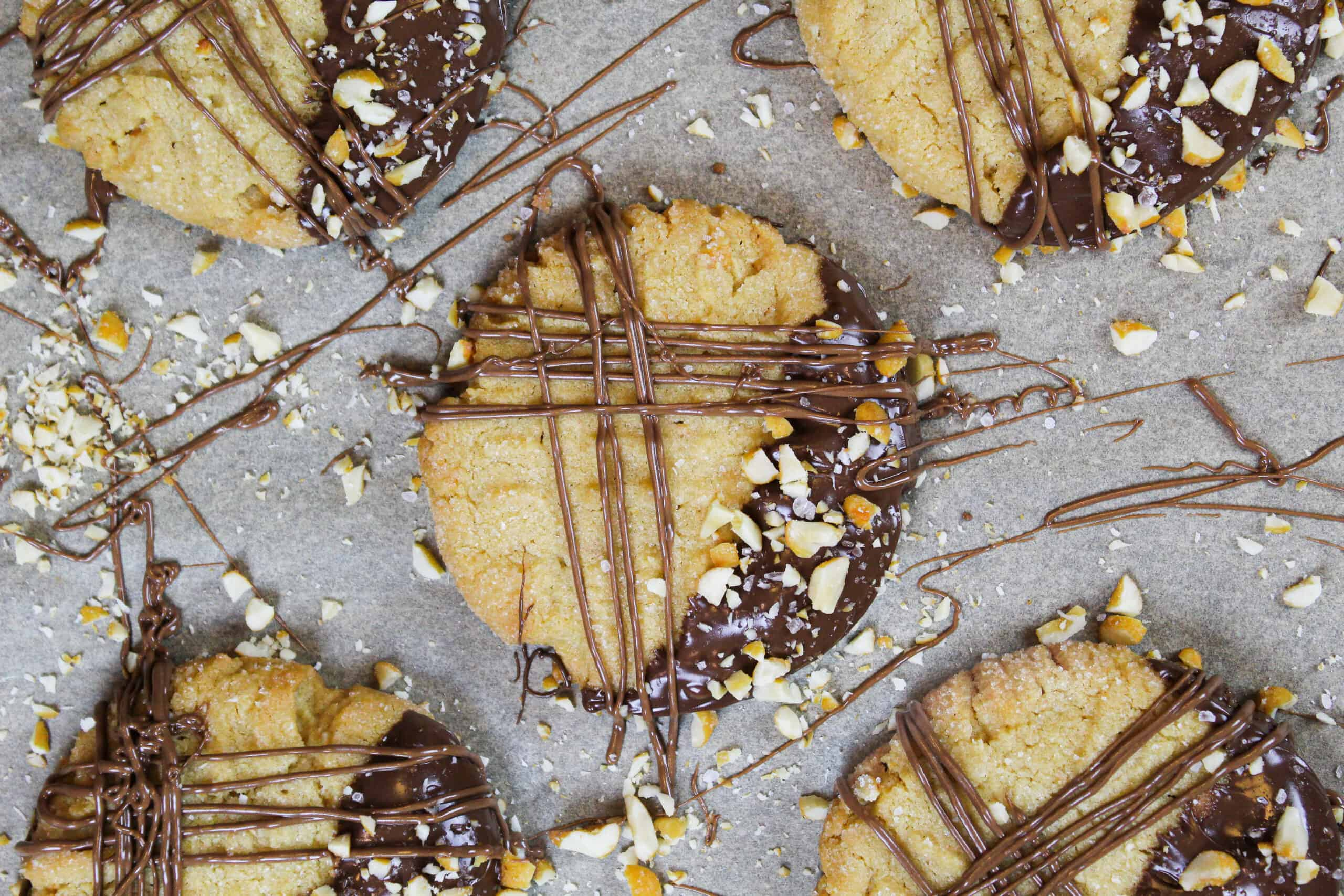 image of chocolate dipped peanut butter cookies decorated with drizzled chocolate