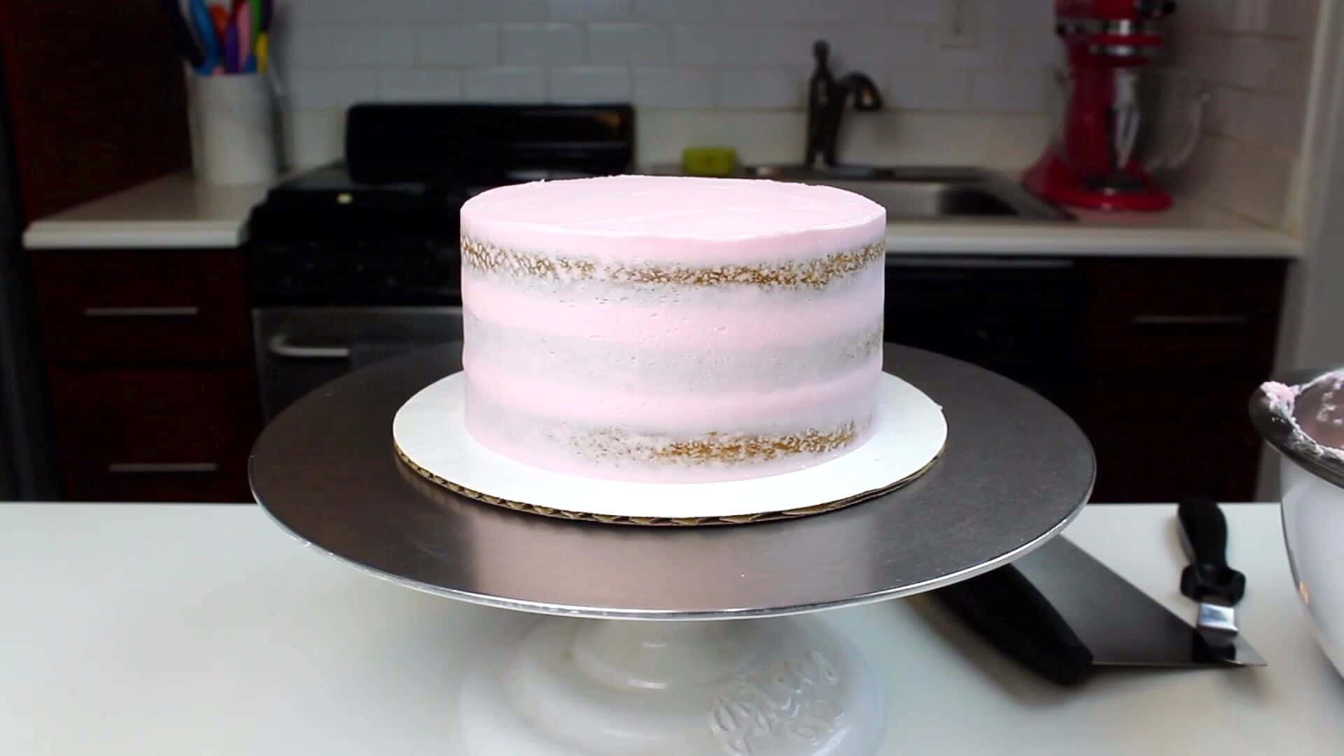 image of a vegan almond cake that has been crumb coated with vegan frosting