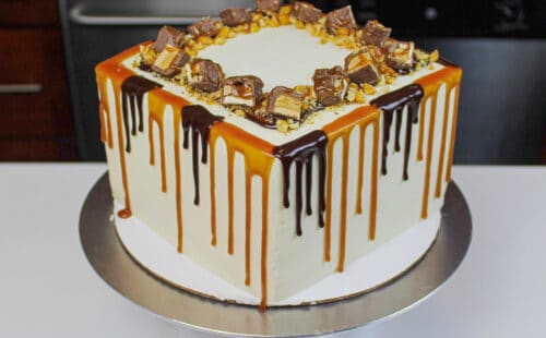 image of snickers drip cake with both a caramel and chocolate drip decoration