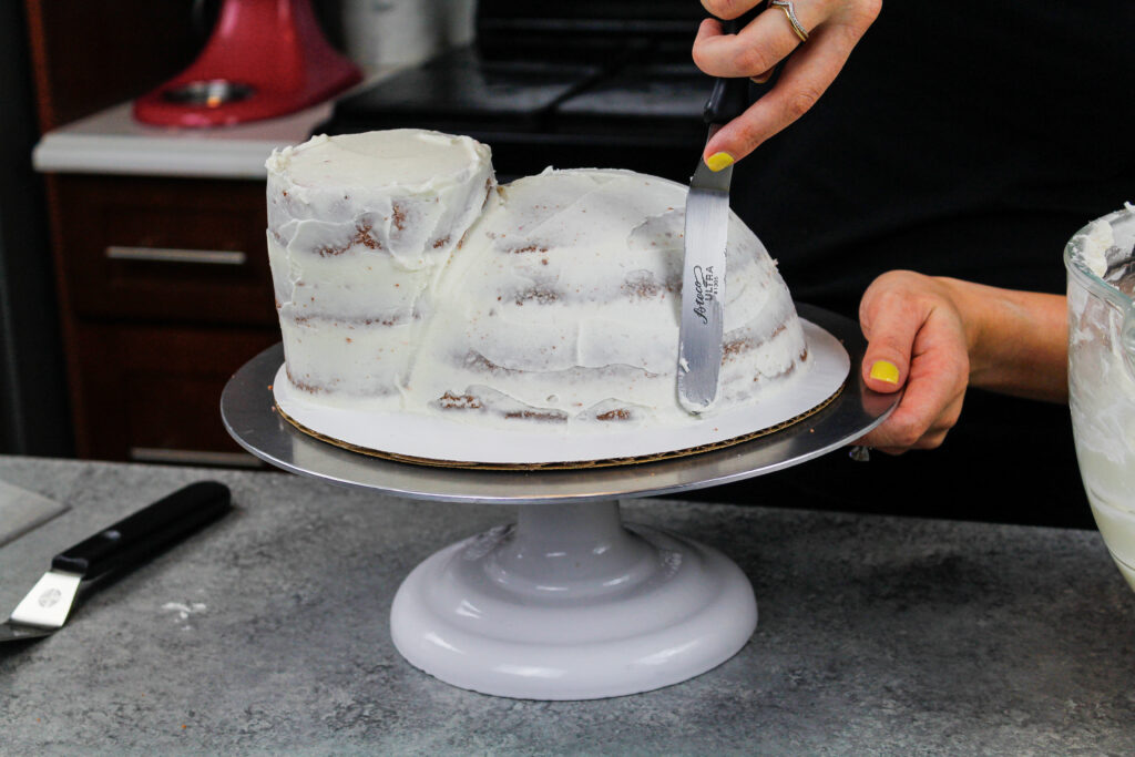 image of a crumb coat being spread on cake layers to make a hippo cake
