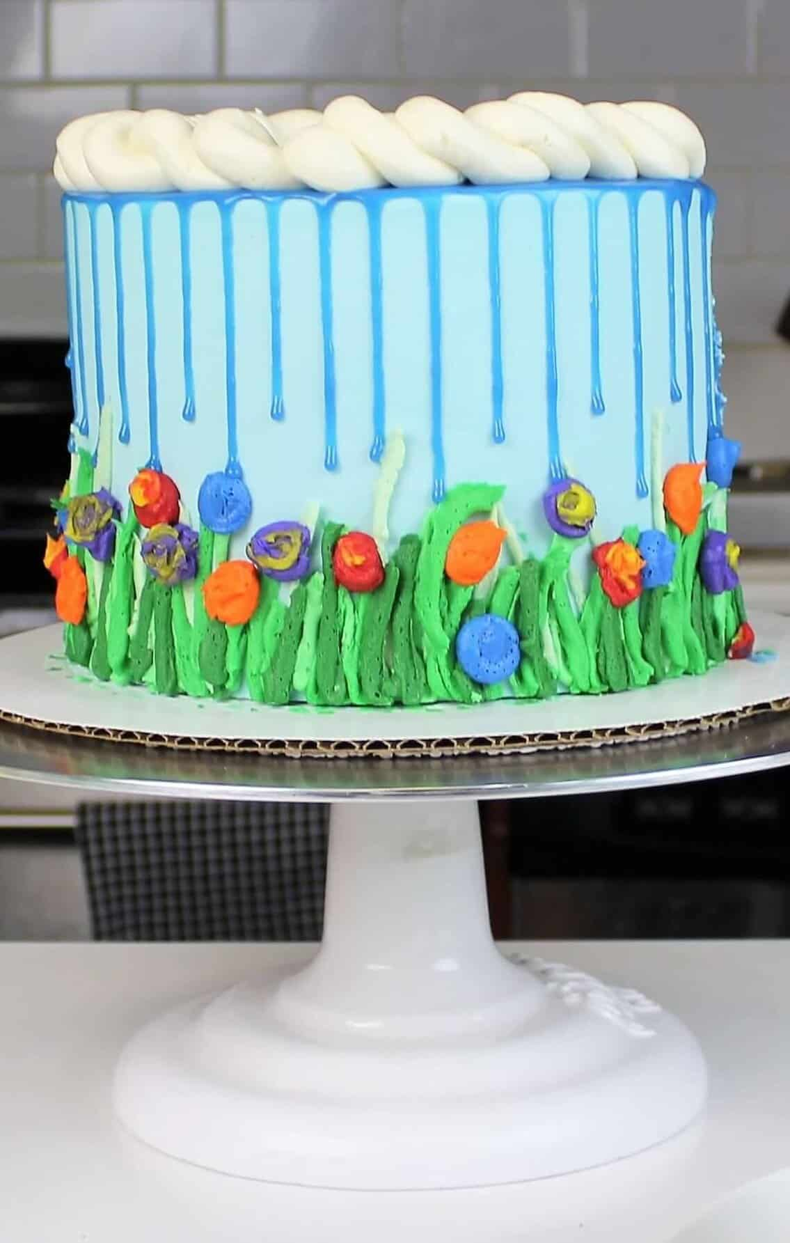 image of spring themed, april showers drip cake made with colorful blue white chocolate ganache drips