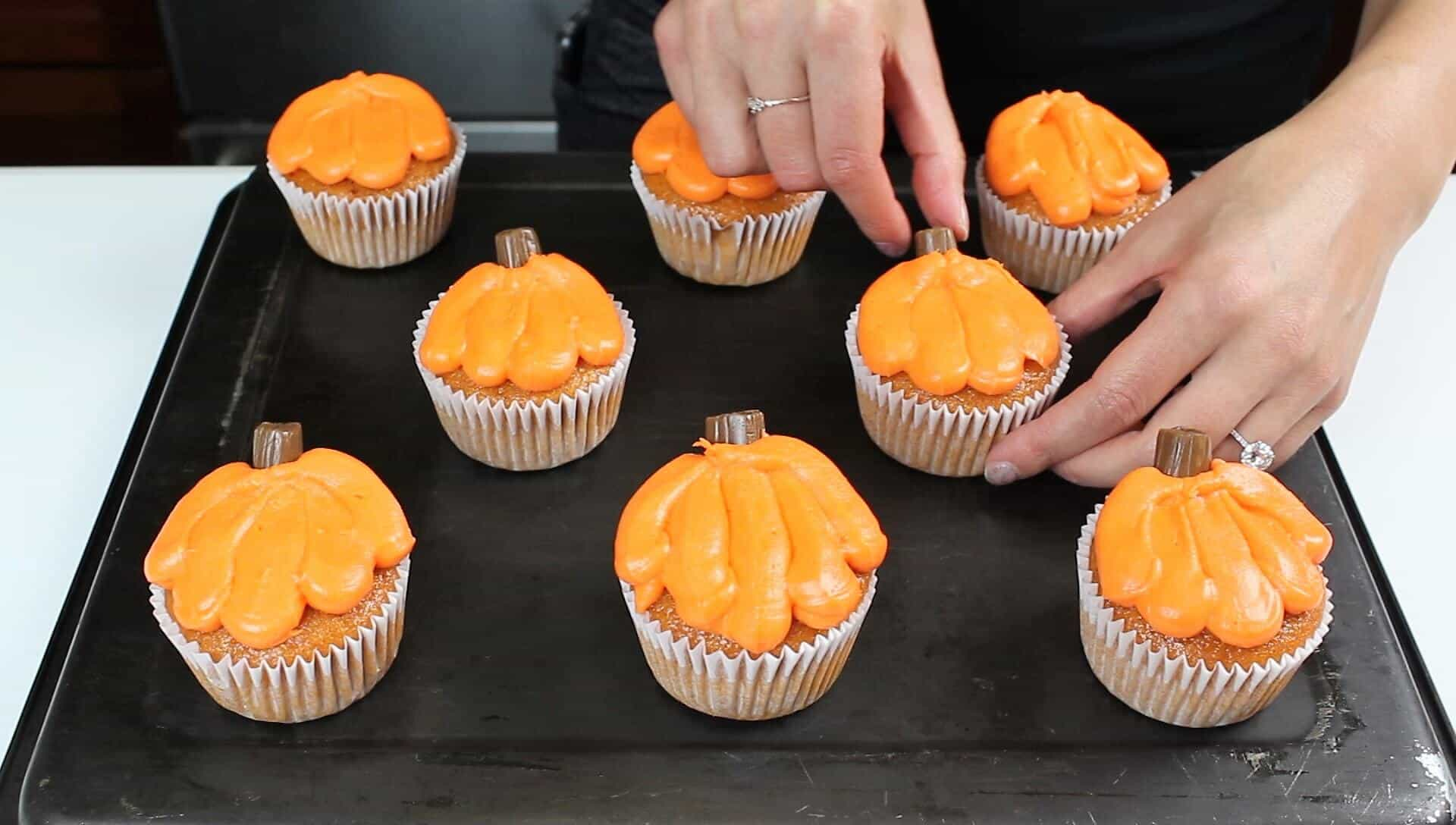 Image of adding tootsie roll stems to the pumpkin cupcakes