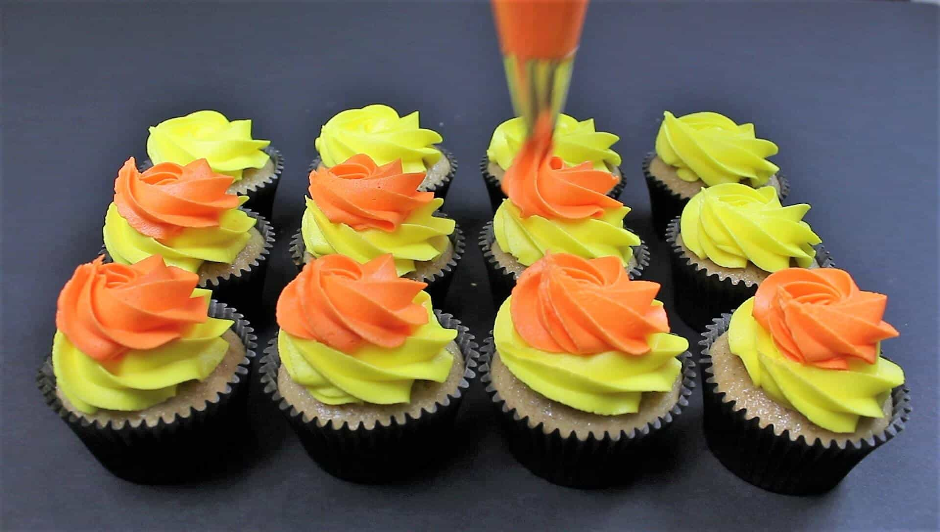 Image of Piping candy corn frosting onto these fireball cupackes