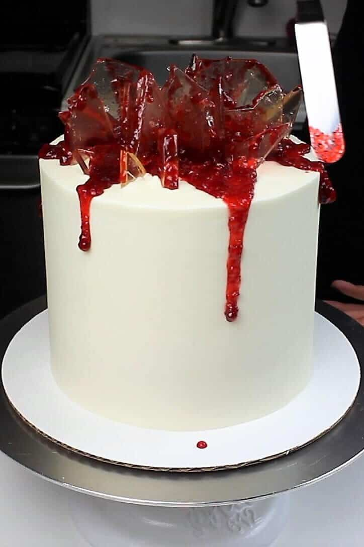 photo of topping this shattered glass cake with edible strawberry jam blood