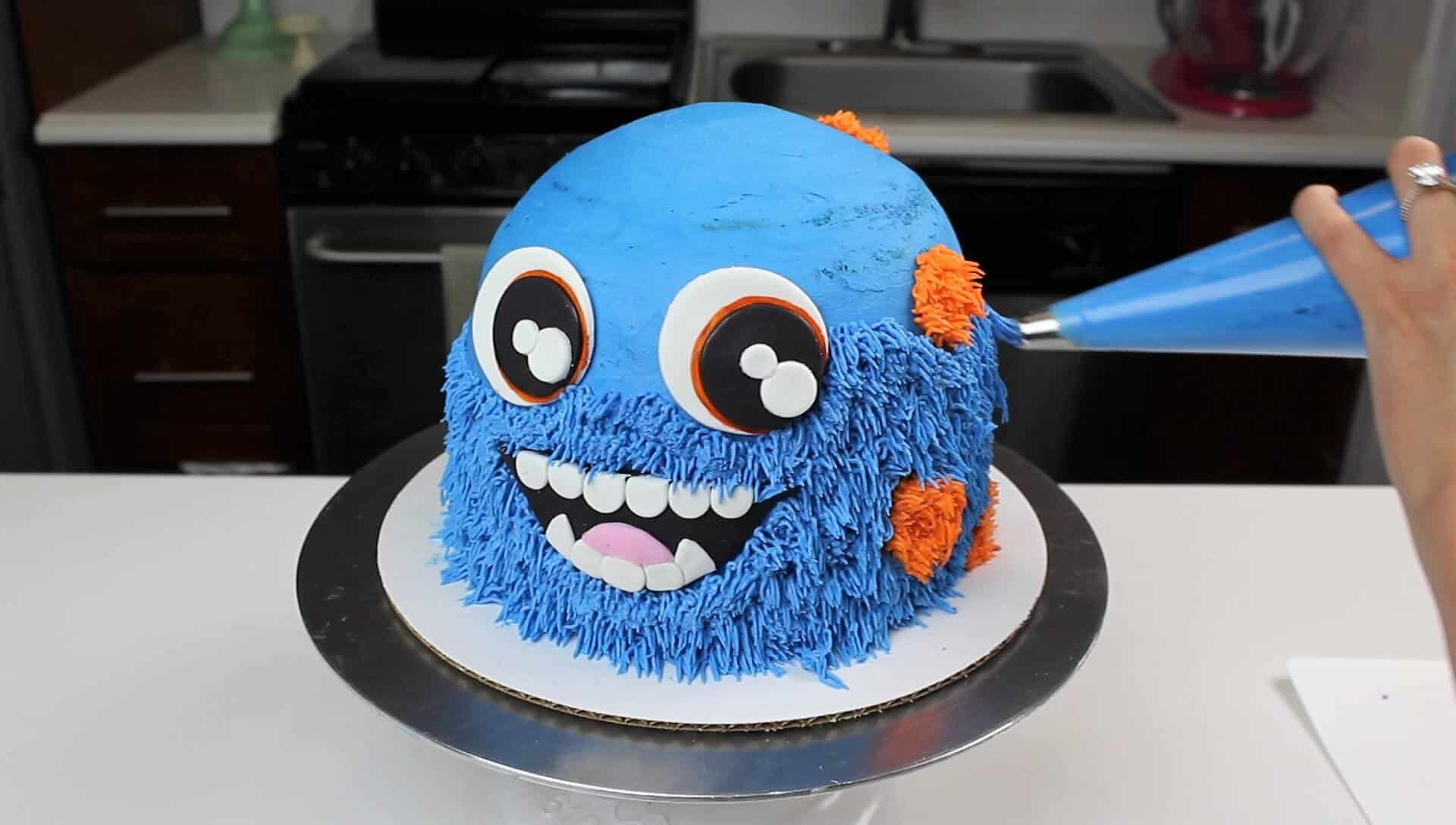 image of piping frosting onto monster smash cake