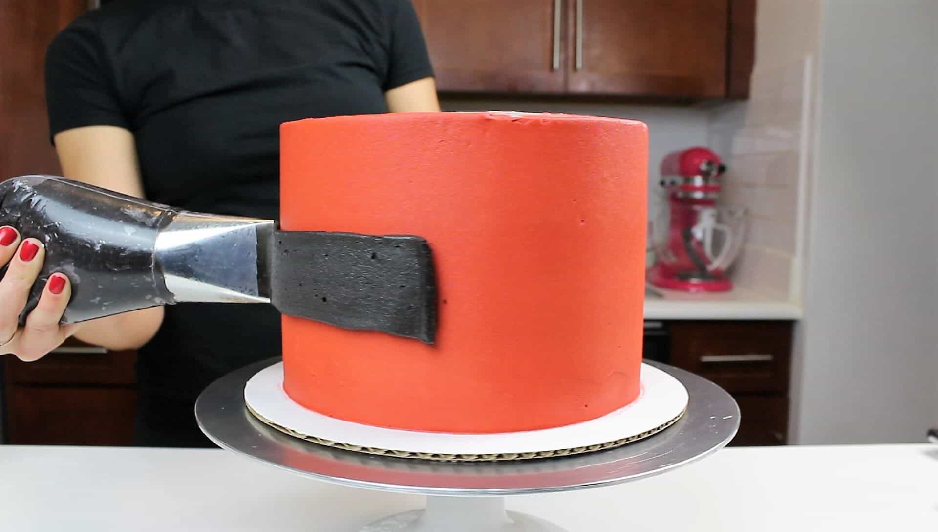 Image of piping black frosting on santa cake to be santa claus' belt
