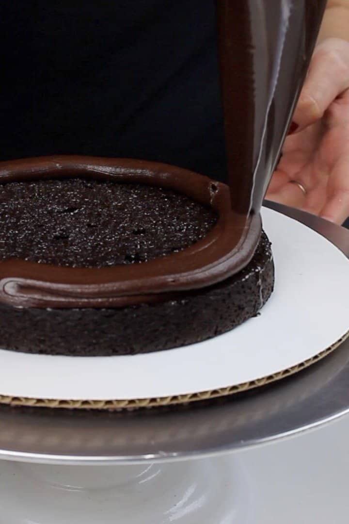 image of piping board of ganache onto chocolate cake