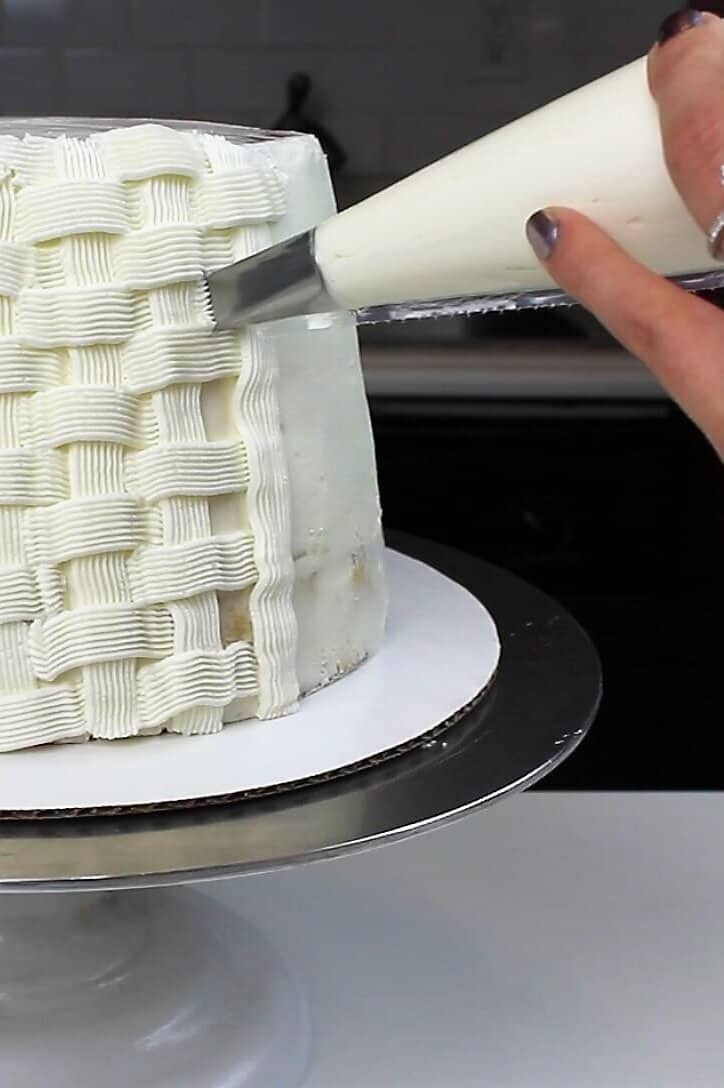 piping a basket weave pattern onto an easter basket cake