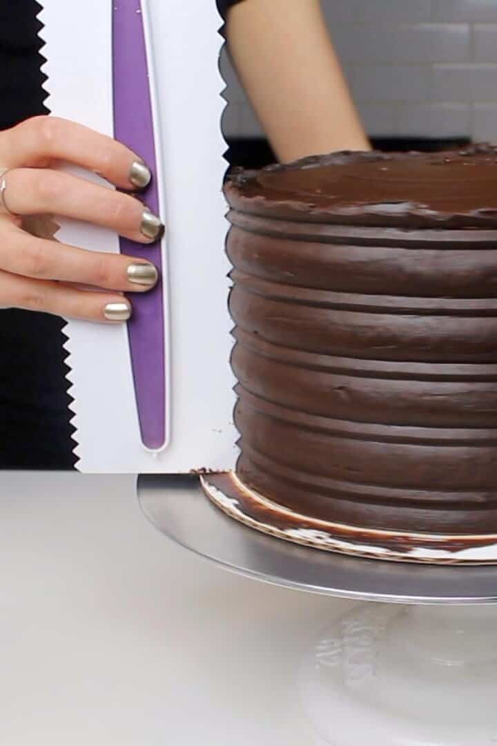 Using a frosting comb to add texture to the sides of this mothers day chocolate cake