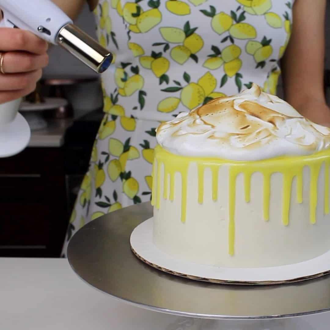 Photo of toasting meringue on top of a lemon meringue drip cake