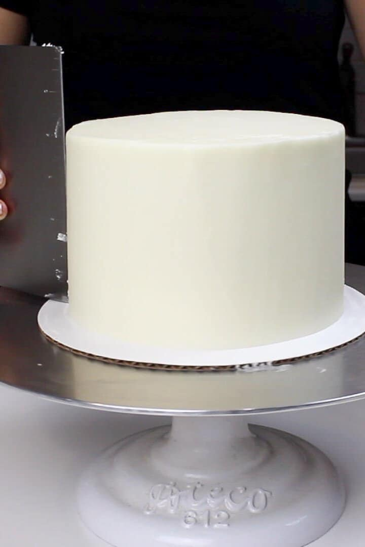 Smoothing Buttercream Onto A Six Inch Vanilla Layer Cake With Bench Scraper
