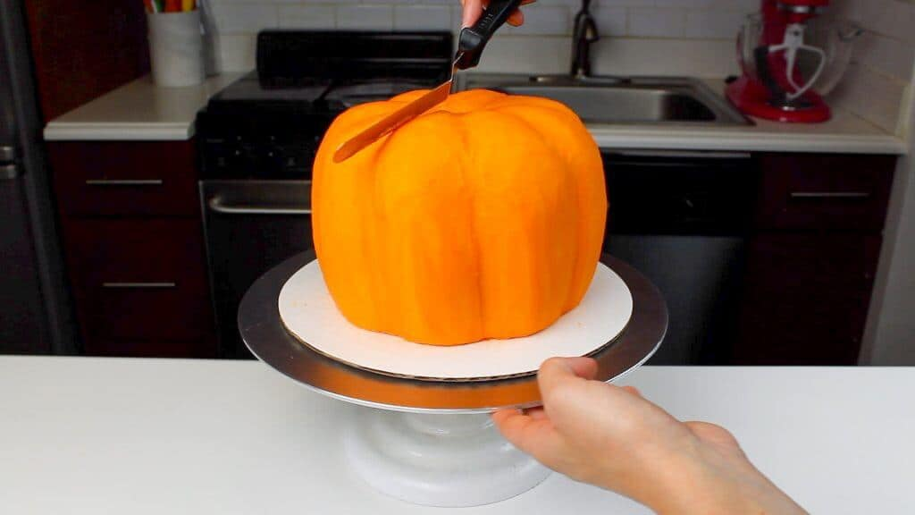 image of smoothing buttercream onto a pumpkin shaped cake