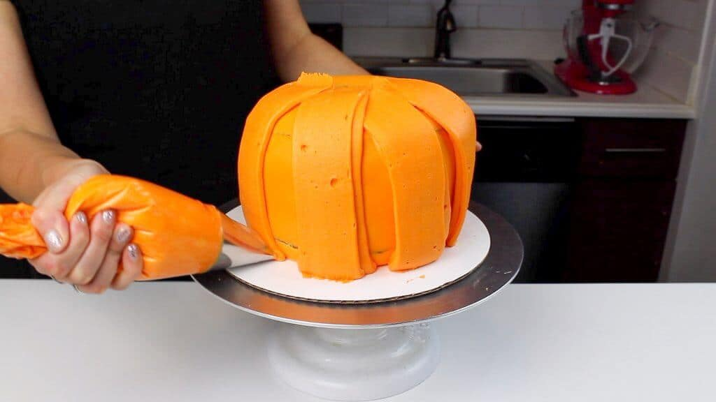 image of piping panels onto pumpkin cake using frosting