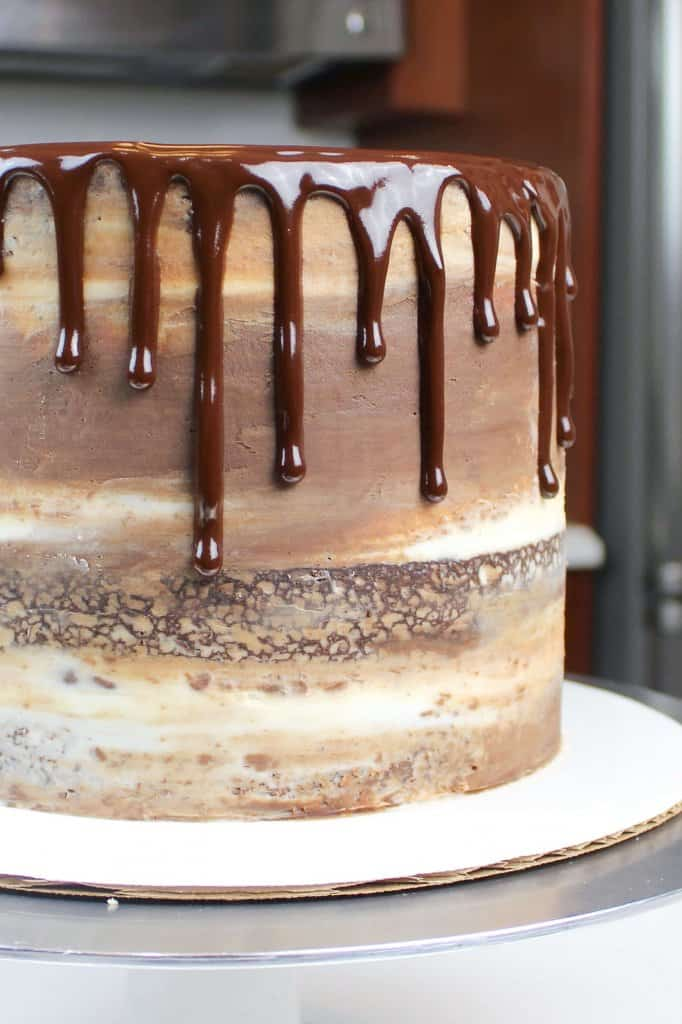 chocolate ganache drips on a semi naked frosted chocolate cake
