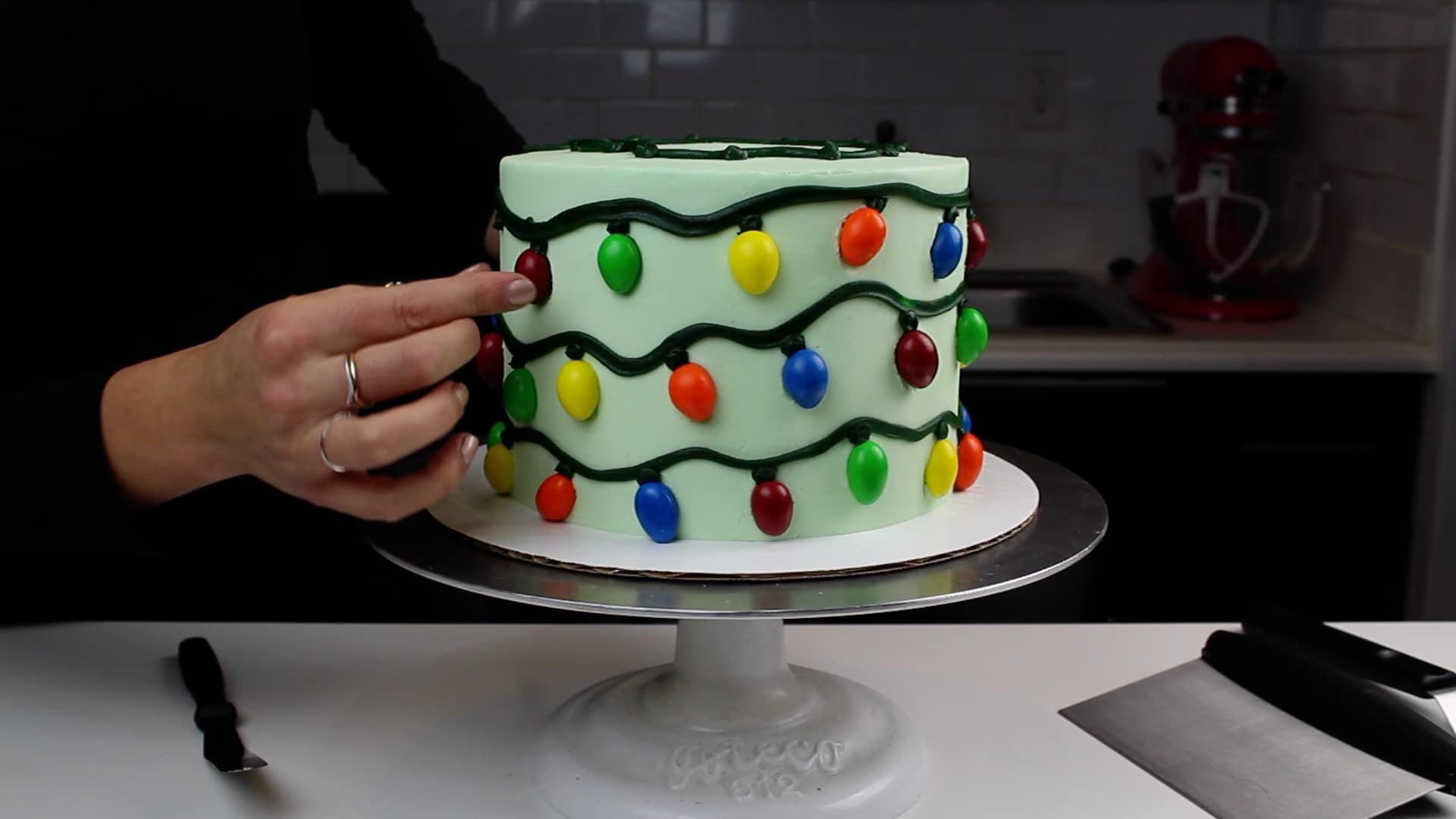 Image of adding Almond M&Ms to cake to look like christmas lights