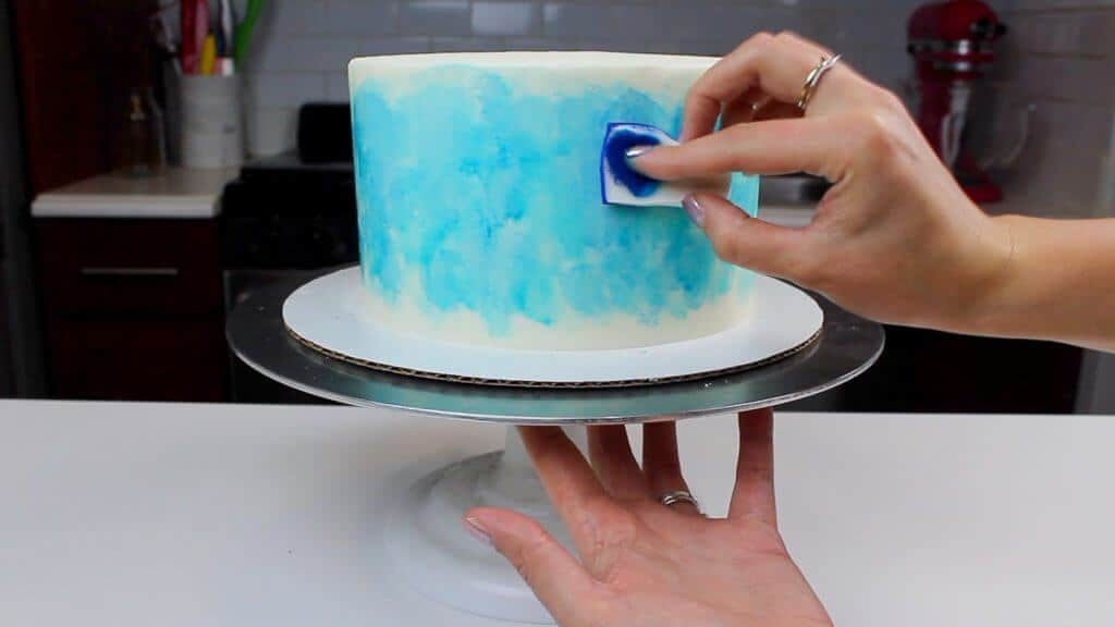 Painting the side of my buttercream cake using a mixture of gel food coloring and vodka