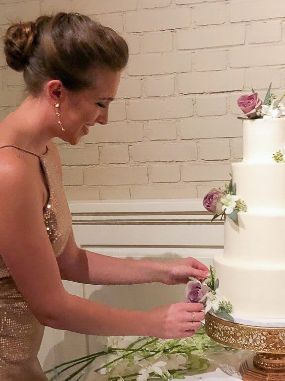 Photo of Chelsey White adding fresh flowers to a wedding cake
