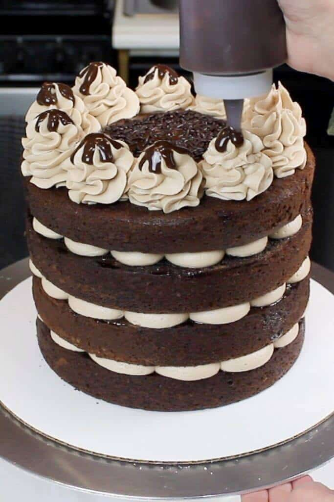 This naked chocolate cake is decorated with whipped chocolate buttercream, and a chocolate ganache drizzle over each swirl.