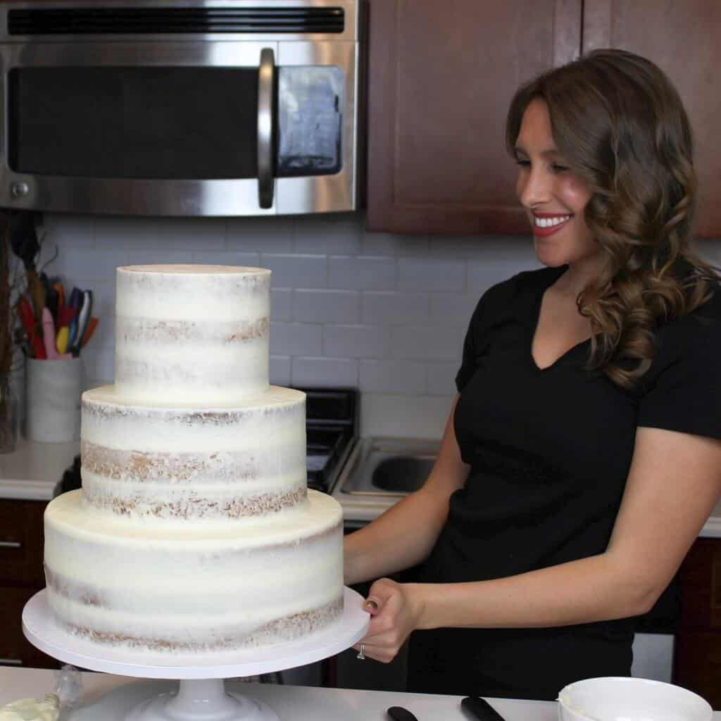 Photo of a three tiered semi naked wedding cake frosted with cream cheese frosting