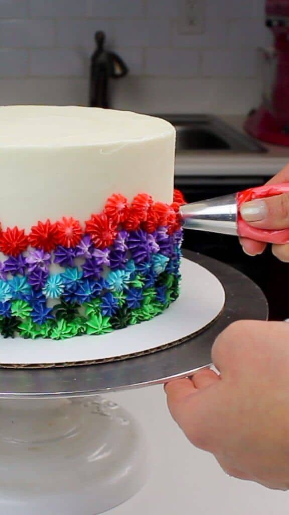 Piping rainbow frosting onto my vanilla cake!
