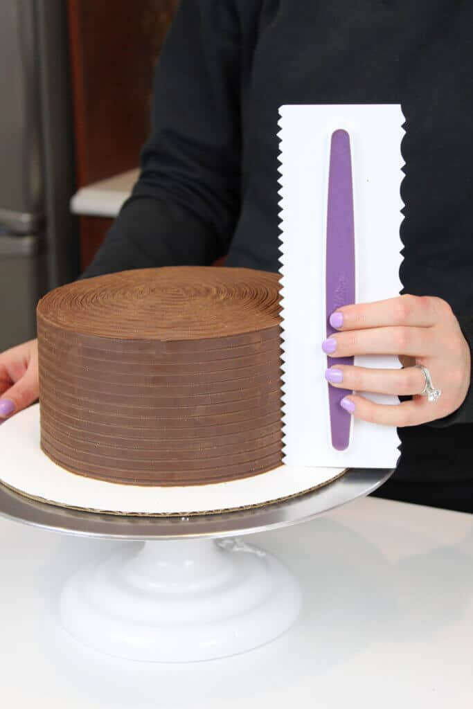 using an icing comb to smooth ganache onto a cake