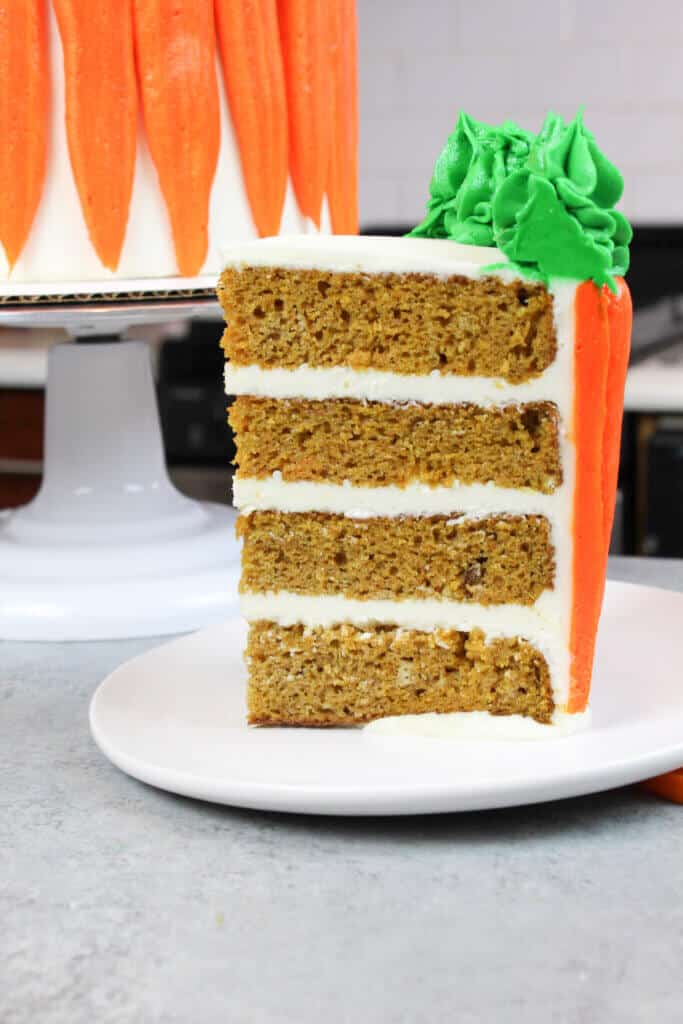 image of slice of carrot cake, showing moist cake layers filled with cream cheese buttercream