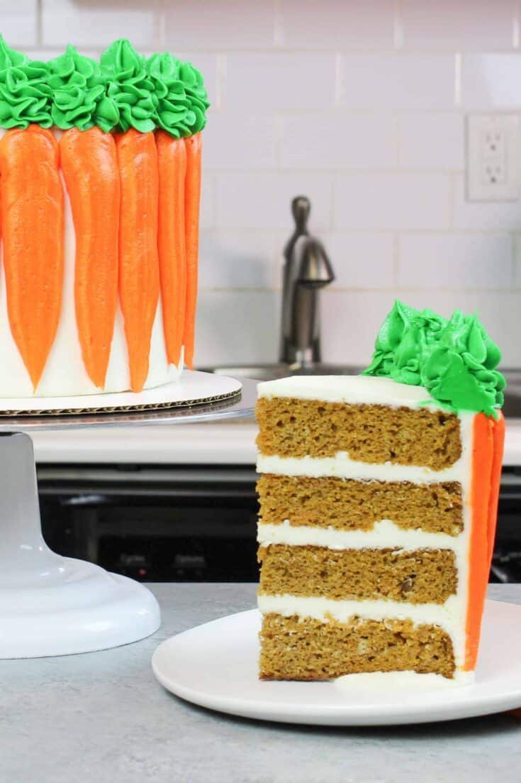 carrot cake slice frosted with cream cheese buttercream, with decorated carrot cake in background
