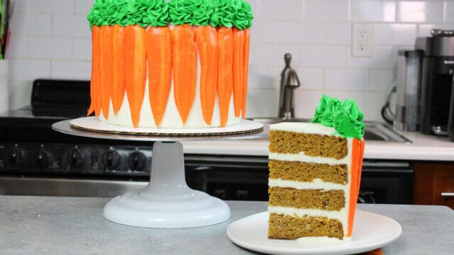 sliced carrot cake decorated with cute buttercream carrots