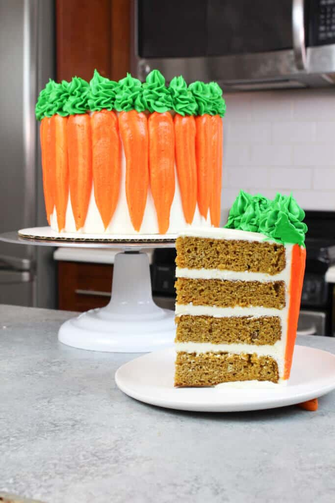 vertical photo of sliced carrot cake, decorated with cute buttercream carrots on the sides