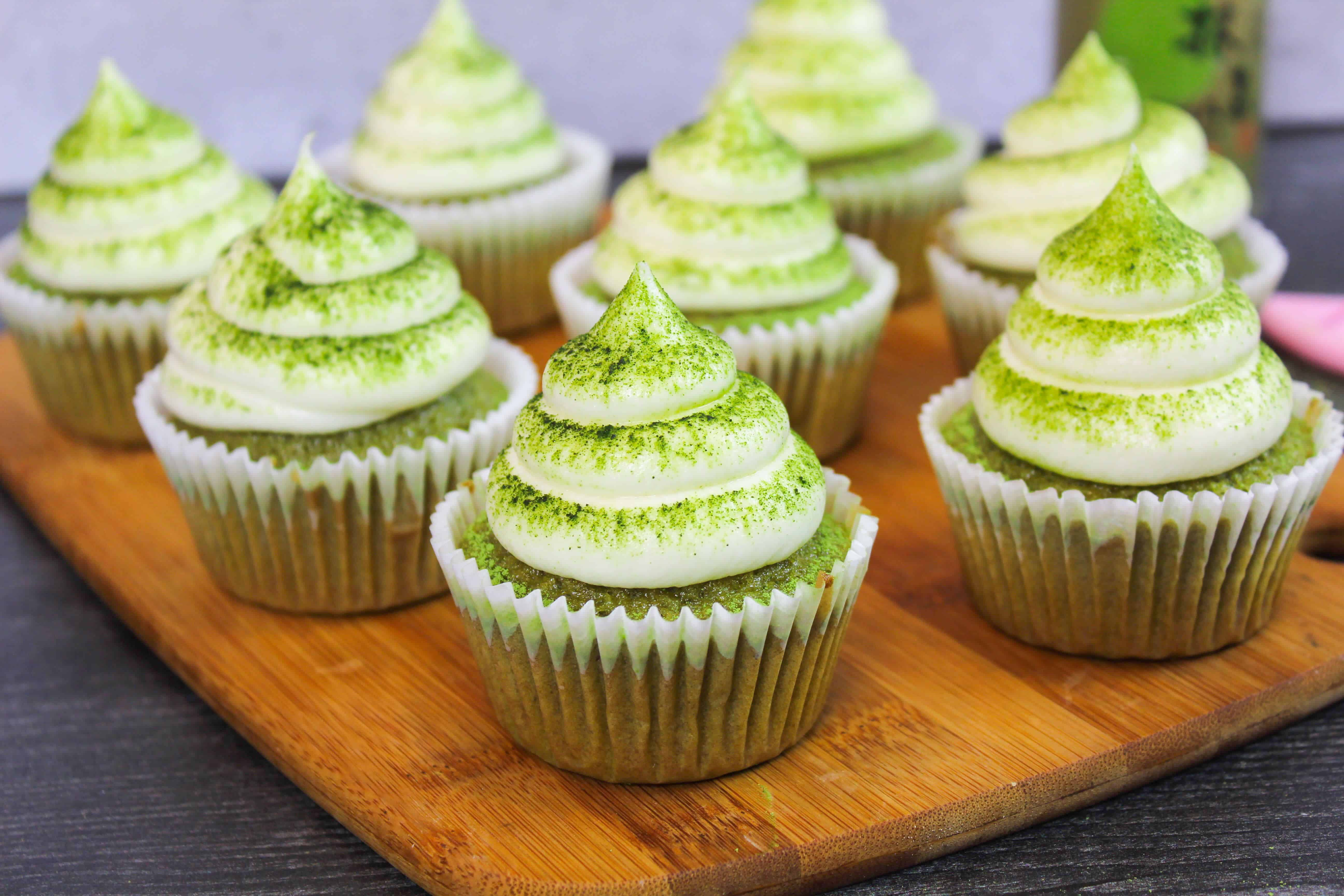batch of matcha cupcakes, frosted with vanilla buttercream, and dusted with matcha powder
