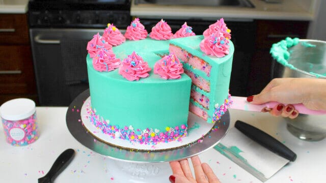 colorful funfetti cake, decorated with teal and pink buttercream and colorful sprinkles