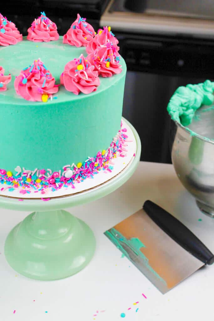 photo of frosted funfetti cake, decorated with turquoise teal frosting and pink frosting swirls
