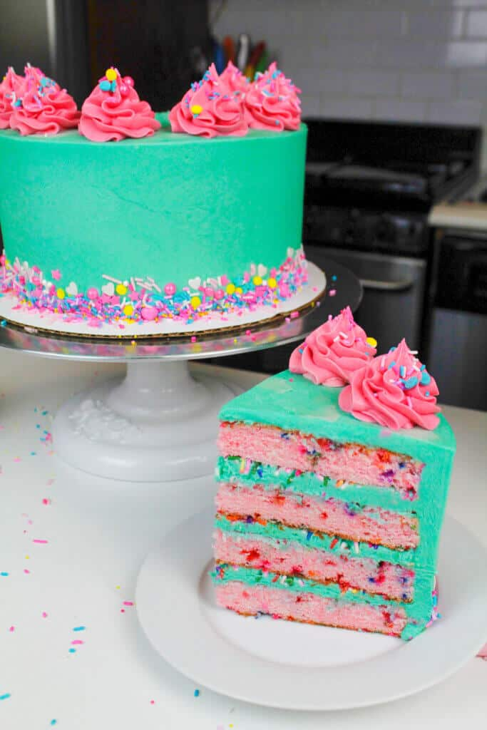 Sliced funfetti cake, with bright blue frosting