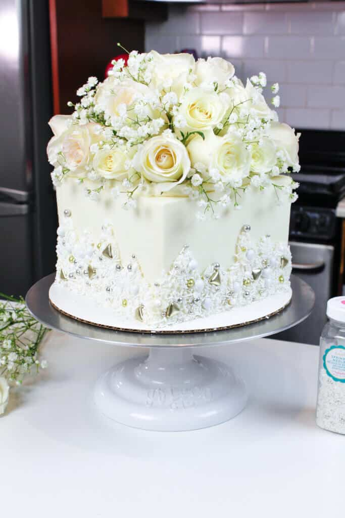 photo of white bridal shower cake, decorated with fresh flowers