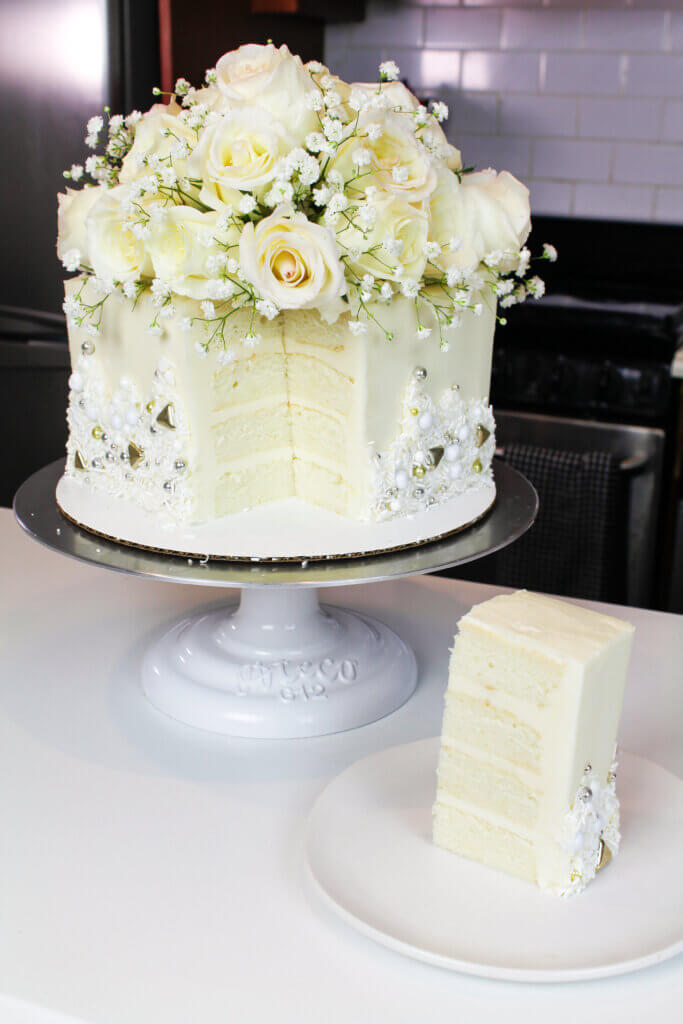 photo of sliced bridal shower cake, decorated with white roses