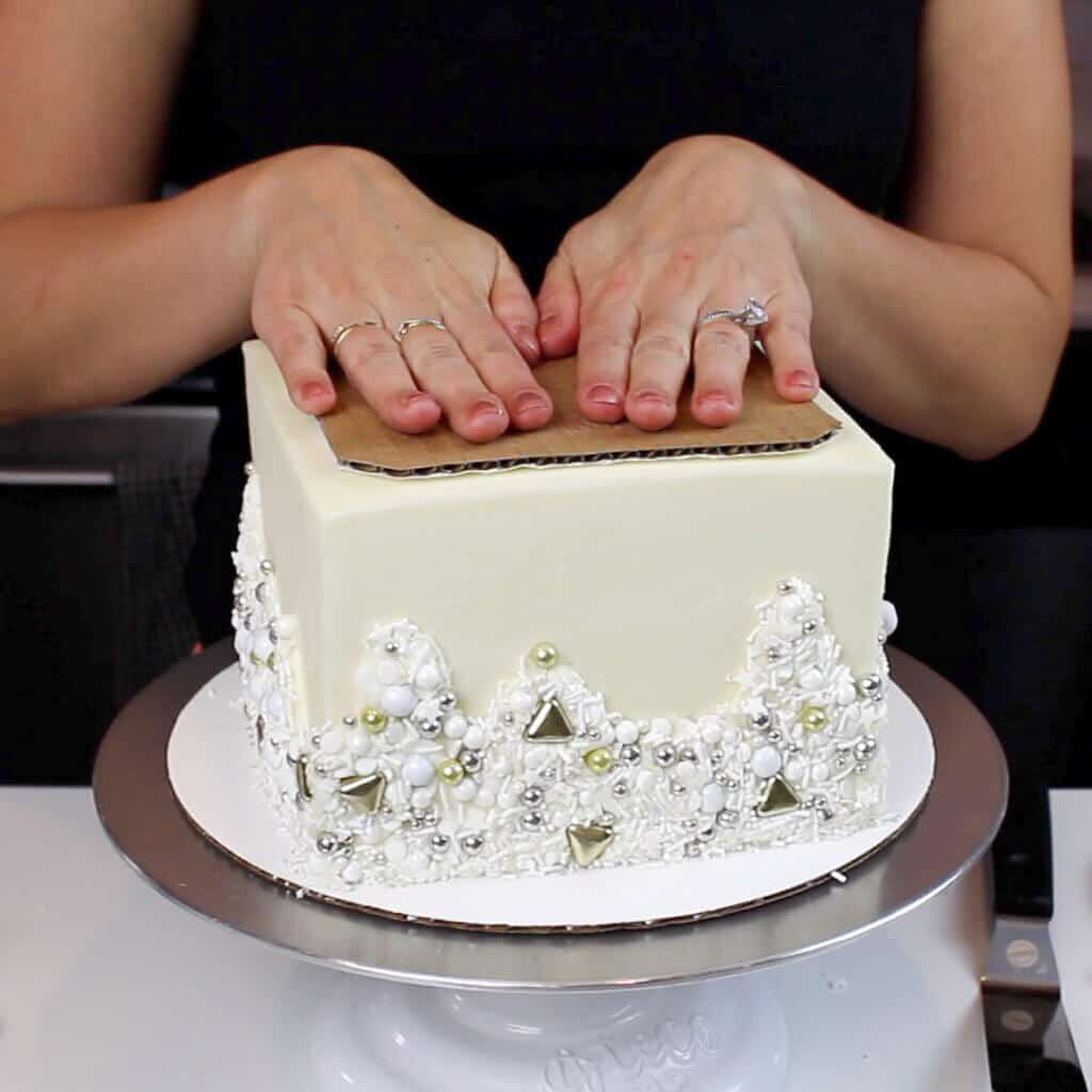placing cardboard cake round on top of the cake photo