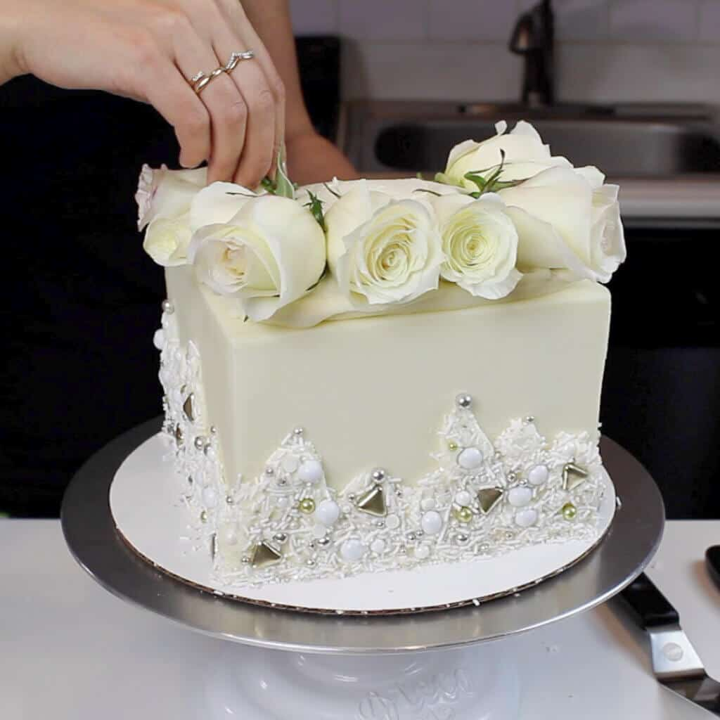 adding fresh white roses to a wedding cake image