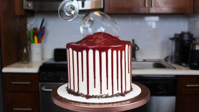 Red wine chocolate cake decorated with red wine drips, on a copper cake stand