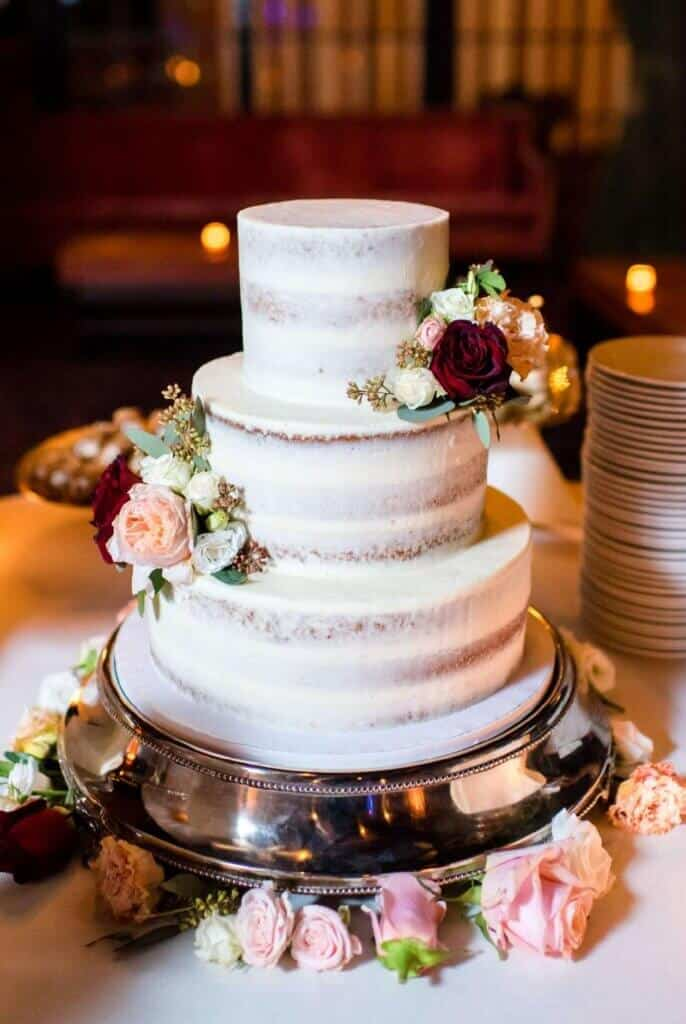 photo of semi naked wedding cake with fresh flowers