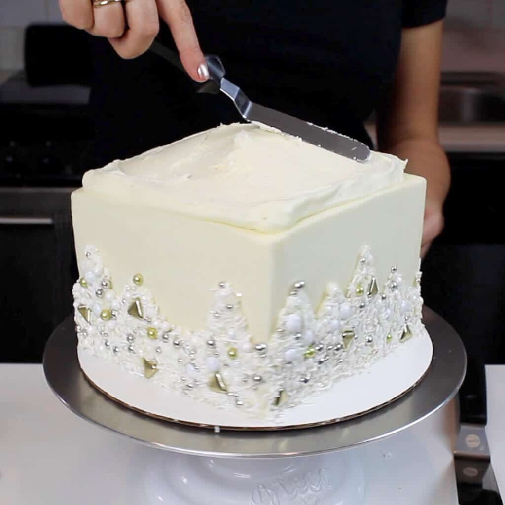 adding frosting on top of a cardboard cake round to put fresh flowers on a cake photo
